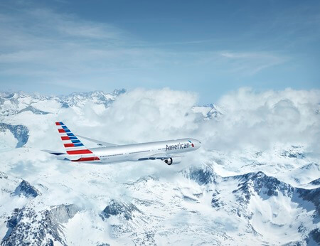 american airlines boeing 777 300er n720an airborne flying over mountains