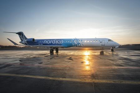 Nordica Bombardier CRJ 900 ES-ACD parking on apron at Tallinn Airport in sunset